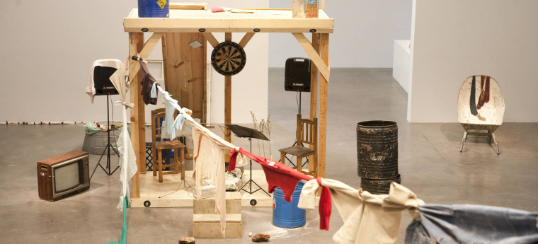 mixed media installation of a wooden shed with common objects: chairs, music stand, television, dart board, clothing tied together resembling a clothesline