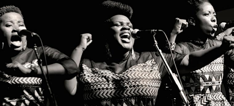 3 women from Zimbabwe singing with microphones; members of the singing group Nobuntu