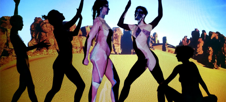 Still image from a video titled Adieu Les Demoiselles by Theo Eshetu; silhouettes of five women in different poses in front of a rock formation