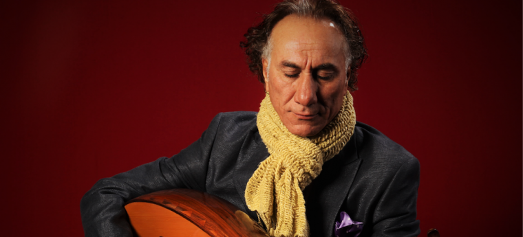 Rahim Al Haj [a middle aged man], wearing a scarf over a suit jacket playing an oud.